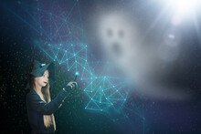 A Girl Dressed As A Witch Weaves A Protective Net From A Ghost. Picture With A Dark Background For Halloween. Mystical Production With Magical Elements
