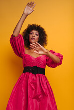Fashionable Medium Shot Of Latin Female Posing Gracefully In Front Of Mustard Backdrop. Woman With Stylish Dark Afro Hairstyle Looking Straight Into The Camera Wearing Bright Raspberry Dress