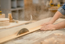 Carpenter Cutting A Piece Of Wood At Workshop, Using A Circular Saw