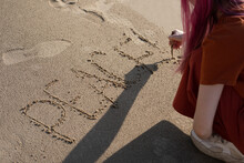 """Woman With Pink Hair On The Beach With A Stick On The Sand Writes The Word """"peace"""""""