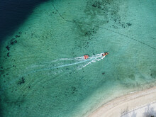 Aerial Shot Of Two Sailboats Swimming On Clear Transparent Water With Sandy Beach