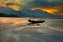A Boat Drawn Ashore On A Sandy Beach In Central Vietnam Coastline, North Of Danang, At Sunset