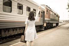 Young Woman In With A Suitcase Waves To The Departing Train. Retro-style Processing. The Concept Of Being Late For A Train And Seeing Off Or Meeting A Young Person From A Train On The Platform.