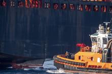 Tug Boat Near Big Ship Stern