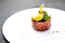 A Horizontal View Of A Salmon Tartar On An Elegant White Plate, On A Black Stony Background. Appetizer Prepared From Fresh Raw Salmon And Seasonings, Decorated With Lime Wedge.