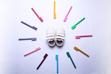 Colorful Markers Form A Circle Surrounding The Kid's Shoes In Isolated White Background. Top View.