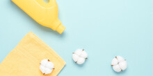 Yellow Plastic Packaging With Laundry Detergent, Liquid Washing Powder, Conditioner, Terry Towel And Cotton Flowers On A Pastel Blue Background. Top View, Flat Lay. Banner