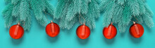 Beautiful Christmas Border. Decorative Spruce Branches With Red Balls On A Turquoise Background. Top View, Flat Lay.