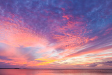 Glorious Beautiful Colorful Sunset With Colors Stringing Out From Horizon Over Ocean With Yellow And Pink Bursting Into Dappled Purple Near The Top
