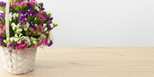 A Basket With Multicolored Statice Flowers Stands On A Wooden Table Top On A Light Background . The Flowers Are Purple, White And Pink . A Banner With Free Space For Your Business .