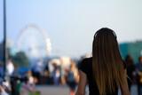 Fototapeta Miasto - Piękna młoda kobieta na tle parku rozrywki