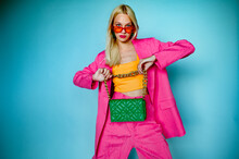 Fashion Portrait Of Confident Woman Wearing Trendy Summer Pink Fuchsia Color Suit, Orange Sunglasses, Holding Green Quilted Faux Leather Bag, Posing In Studio, On Blue Background. Copy, Empty Space