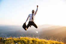 Businessman Jumps For Joy Over The Hill.