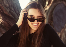 Beautiful Toothy Laughing Winking Woman Looking Happy In Fashion Sunglasses Outdoors Summer Green Trees Background. Closeup Portrait