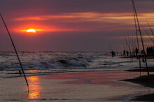 Fishermen With Their Fishing Rods Ready To Fish On A Sunset At The Seashore.