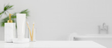 White Tabletop With Toothbrush, Shampoo Bottle, Body Lotion Tube Over Bright White Bathroom Interior
