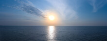 Panorama Of Sunrise On The Sea. Small Waves On The Water And A Cloudy Sky With Orange Sun.