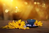 Fototapeta Kwiaty - filiżanka kawy w jesienny poranek, kawa o poranku, żółte kwiaty słonecznika