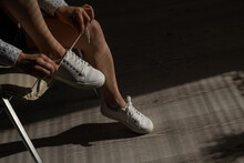 Woman Put On New White Leather Sneakers