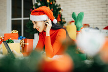 Beautiful Smiling Happy Woman In Red Dress And Wearing A Santa Hat Is Lying On The Ground Surrounded By Colorful Gift Boxes With A Christmas Tree In The Background Holding Tablet In Hand.