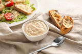 Bowl of tasty Caesar sauce and croutons on table