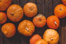 A Bunch Of Ripe Pumpkins Lie On A Wooden Platform