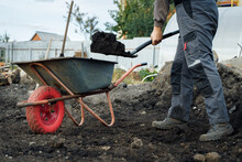 Working With Garden Tools, Shovel And Wheelbarrow On The Site Of A Country House. Preparation For Construction Work.