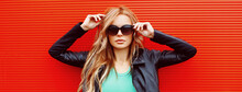 Stylish Portrait Of Beautiful Blonde Woman Wearing A Black Rock Jacket And Sunglasses On Red Background