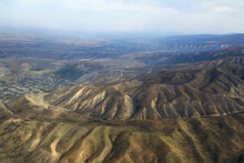 Top View Of A Chain Of Mountain Ranges Of Talgar Mountai In Autumn,a Road Passes Through The Gorge, Settlements Are Visible, Good Weather, Sky With Clouds, Haze, Aerial Photography. Aerial Photography