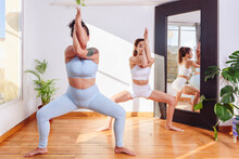 Tranquil Women Practicing Yoga In Goddess Position