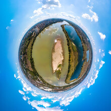 Little Planet Aerial Panorama Over A Sandy Island With Sparse Greenery In The Bed Of A Wide River Near The Big City Of Krasnodar On A Sunny Summer Day