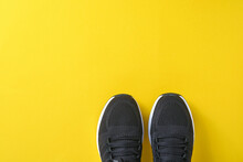 Black Men Sneakers On Yellow Background. Fashion Blog Or Magazine Concept. Men Shoes, Trendy Sneakers, Fashion, Lifestyle. Mock Up. Flat Top View Copy Space Minimal Background.