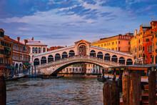 Sunset View Of Famous Bridge Of Rialto Or Ponte Di Rialto Over Grand Canal, Venice, Italy. Iconic Travel Destination Of UNESCO World Heritage City