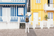 Inspired Traveler Observing Colorful Buildings On Shore