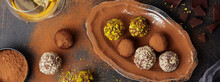 Variety Of Homemade Dark Chocolate Truffles With Cocoa Powder, Pistachios, Almonds In Dark Brown Background Texture. Top View, Copy Space.