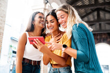 Three Happy Friends Watching A Smart Phone Mobile Outdoors - Millennials Women Using Cellphone On City Street - Technology, Social, Friendship And Youth Concept