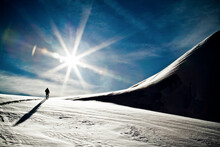 Rear View Of Silhouetted Person Ski Touring Towards Snowy Mountain.