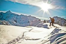 Man Wearing Snowshoes Jumps Off A Mountain Ridge.