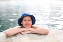 Portrait Of Woman With Blue Hat Resting At Edge Of Hot Springs Pool