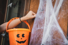 Cropped View Of Girl Holding Bucket With Painted Spooky Face While Knocking At Door Near Decorative Spider Net