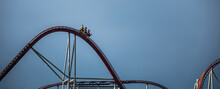 The Train With Some People Is Riding On Roller Coaster During A Cloudy Weather