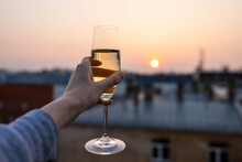 Girl Holding A Glass Of Champagne Into The Sunset.