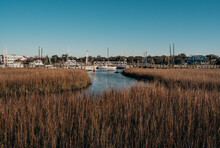 Water Marsh View With Boats And Boardwalk With Sunny Sky