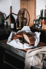 Loaf Of Artisan Sourdough Bread In Wrapping Paper In Kitchen Interior