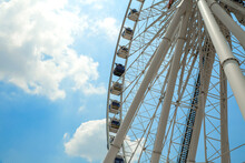 Giant Ferris Wheel With Numbered Cabins In The Park - Bright Blu