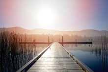 Beautiful Sunrise Over A Lake And Dock, Mountains In Background.