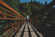 Teen Boy Stands At The End Of A Rust Colored Bridge In The Early Eve
