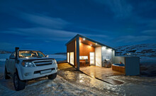 Pick Up Truck Parked Outside Of Illuminated Holiday Home In Iceland