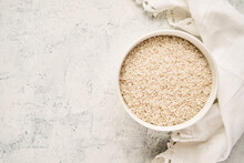 Top View Of A Bowl Filled With Raw White Rice On A Textured Background