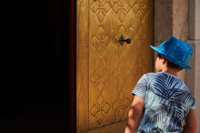 Kid In A Blue Cap Peering Into A Dark Place With A Gold-colored Door. Curiosity Concept